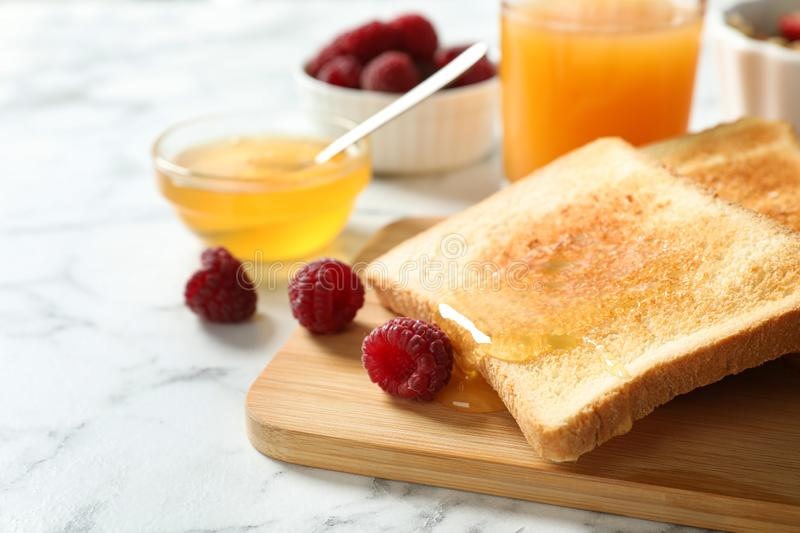 Delicious breakfast with toasted bread, honey and berries on white marble table. Closeup stock photos
