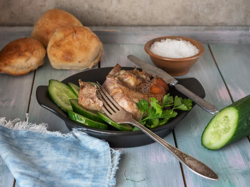 Delicious breakfast of turkey steak with fried potatoes, fresh cucumber boards, bread rolls royalty free stock image