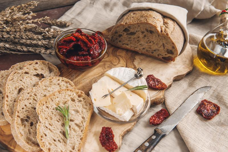 Delicious brie cheese Camembert with sun-dried tomatoes with olive oil and homemade bread. Traditional quick snack for home royalty free stock image