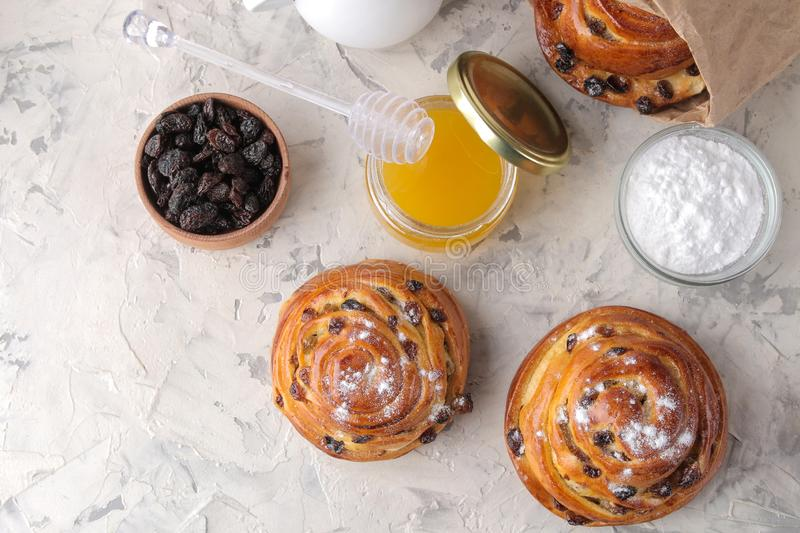 Delicious buns with raisins and honey, powdered sugar on a light concrete table. fresh bakery. breakfast. bread. top view stock image