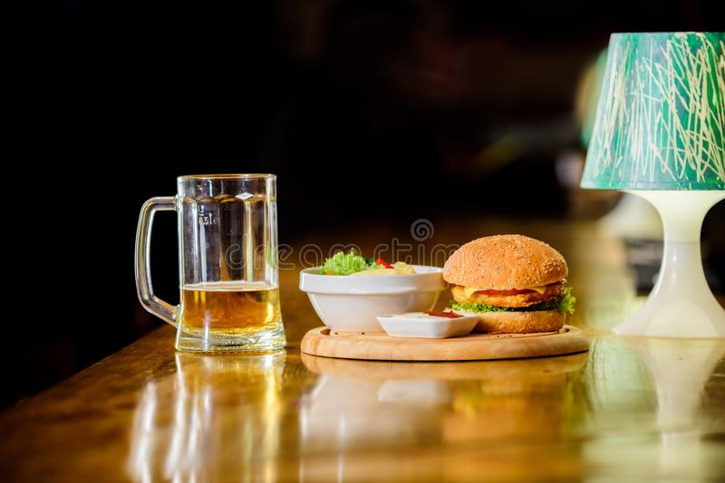 Delicious burger. Burger with cheese meat and salad. Pub food and mug of beer. Fast food concept. Burger menu. High. Calorie snack. Hamburger and french fries royalty free stock photos