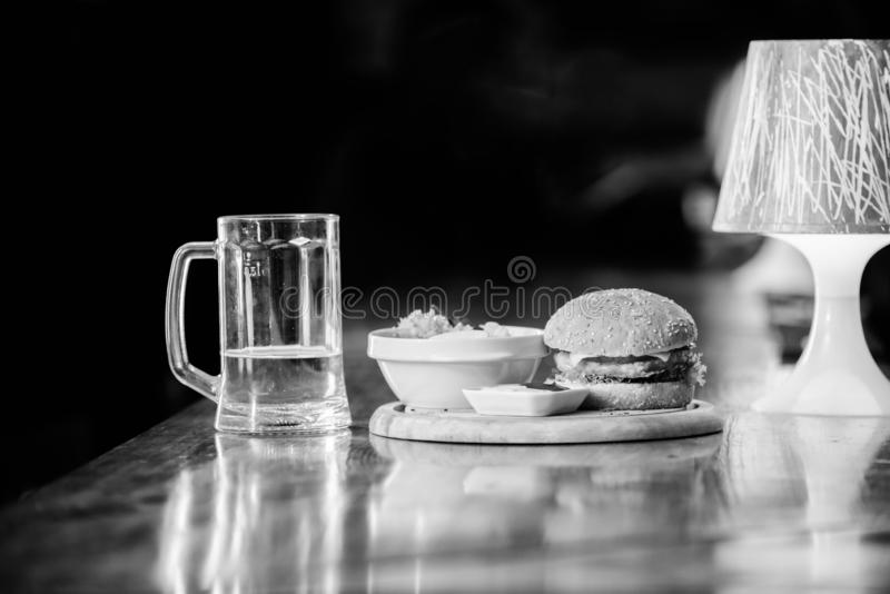 Delicious burger. Burger with cheese meat and salad. Pub food and mug of beer. Fast food concept. Burger menu. High. Calorie snack. Hamburger and french fries stock photos