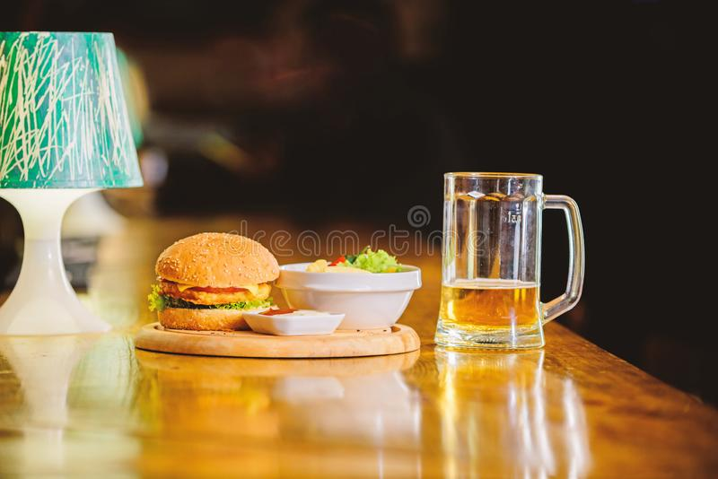 Delicious burger. Burger with cheese meat and salad. Pub food and mug of beer. Fast food concept. Burger menu. High. Calorie snack. Hamburger and french fries royalty free stock photography