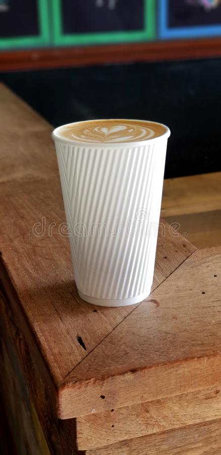 Cafe Latte with Heart Design in White Striped Coffee Cup. Delicious café latte drink served in a white paper cup with raised stripes that act as a cool royalty free stock image