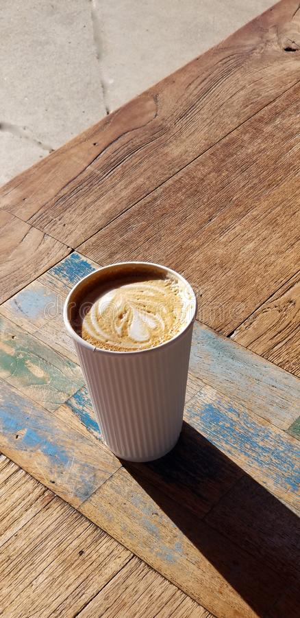 Cafe Latte with Heart Design in White Striped Coffee Cup. Delicious café latte drink served in a white paper cup with raised stripes that act as a cool stock photography