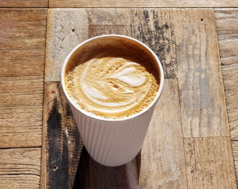 Cafe Latte with Heart Design in White Striped Coffee Cup. Delicious café latte drink served in a white paper cup with raised stripes that act as a cool stock photos