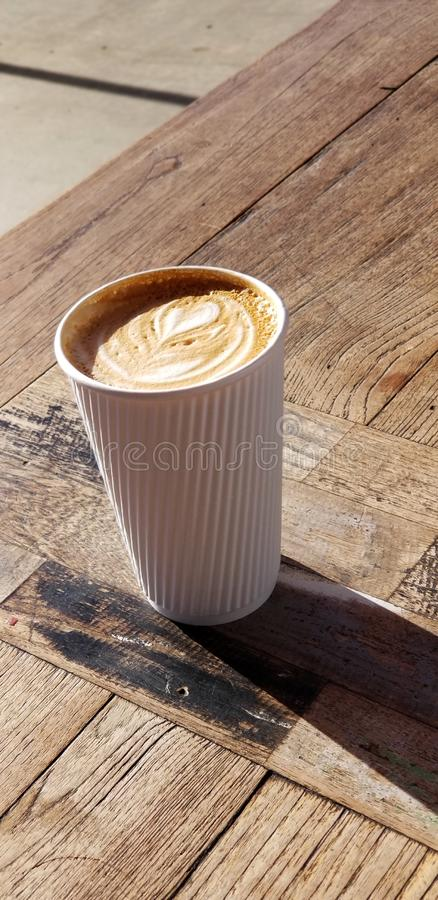 Cafe Latte with Heart Design in White Striped Coffee Cup. Delicious café latte drink served in a white paper cup with raised stripes that act as a cool stock image