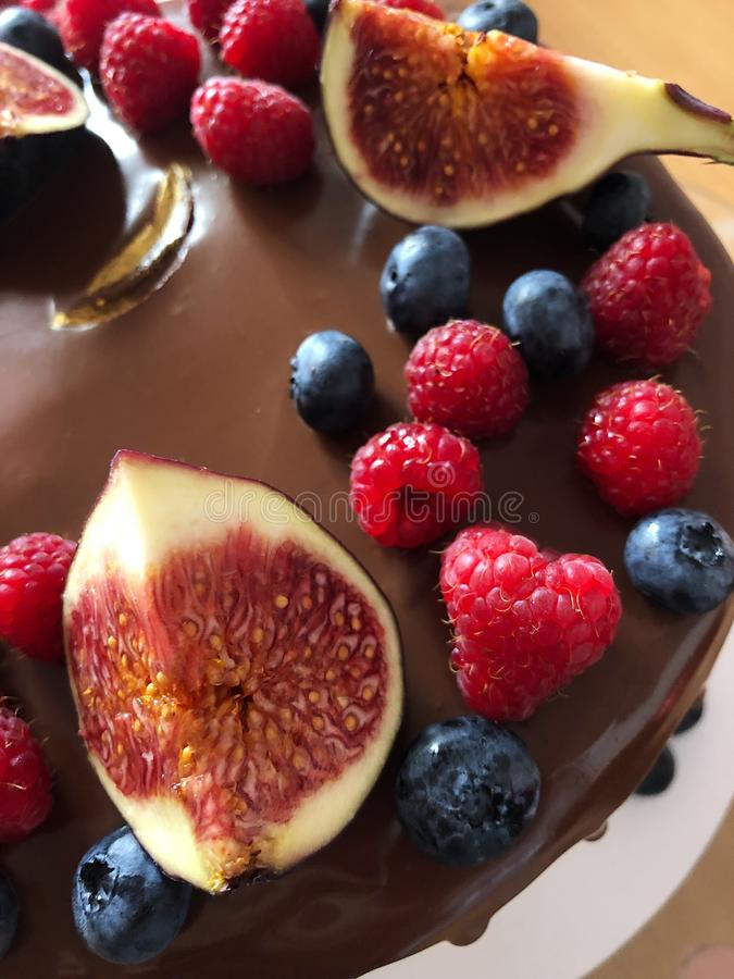 Delicious cake with berries and figs on the table royalty free stock photography