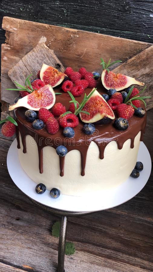 Delicious cake with berries and figs on the table stock photography