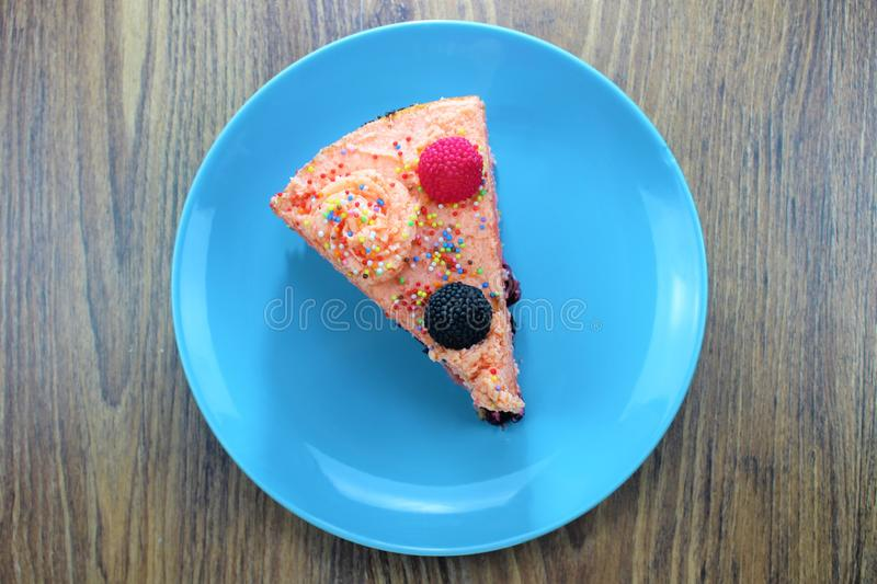 Delicious cake on a blue and white plate with chocolateTasty cake with strawberries, blackberries and colorful sprinkles on the bl royalty free stock photos