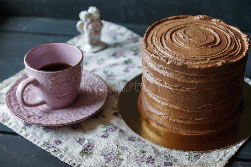 Delicious cake in chocolate sauce with cup of tee. On tender tablecloth stock photos