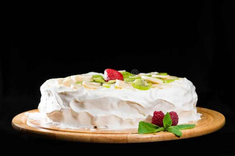 Delicious cake with custard, strawberries, kiwi, bananas, raspberries and mint on wooden plate isolated on dark background royalty free stock photography