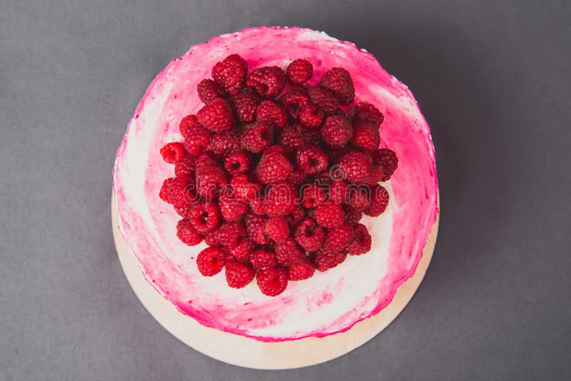 A delicious cake decorated with raspberries on a gray background. stock images