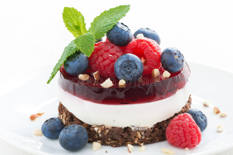 Delicious cake with fruit jelly, nuts and fresh berries. On a plate, close-up, horizontal stock photos