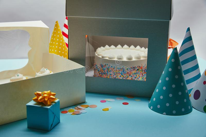 Delicious cake with meringues in box, cupcakes, gift and party hats. On table stock images