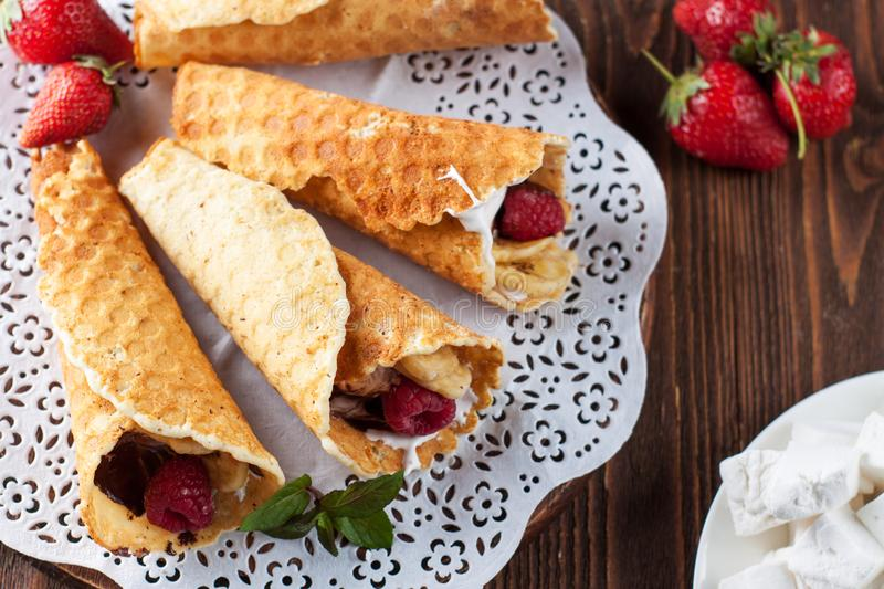 Campfire Cones with berries. Delicious Campfire Cones filled marshmallow, chocolate, banana chips and fresh berries royalty free stock photography
