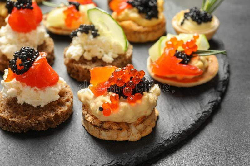 Delicious canapes with black caviar on slate plate,. Closeup stock photo