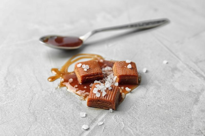 Delicious candies with caramel sauce and salt. On light background royalty free stock photography