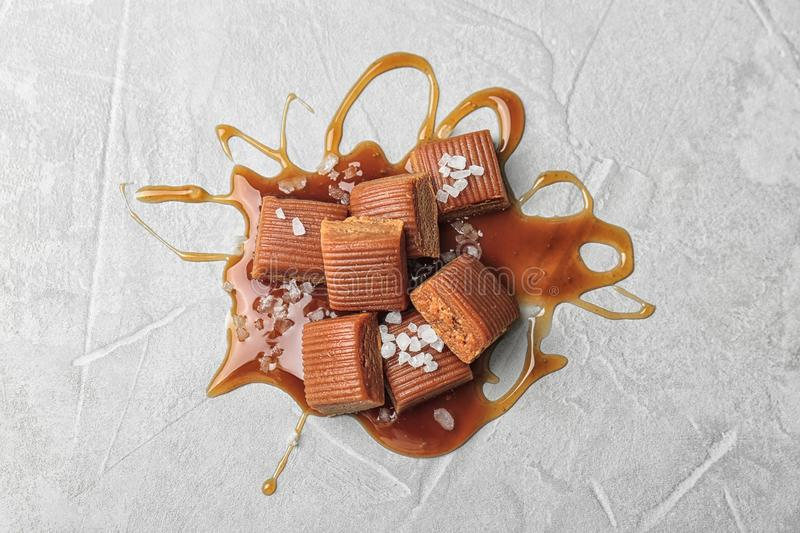 Delicious candies with caramel sauce and salt. On light background, top view stock photography