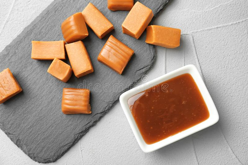 Delicious candies and caramel sauce on table. Top view royalty free stock images