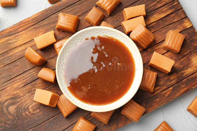 Delicious candies and caramel sauce on wooden board. Top view stock photo