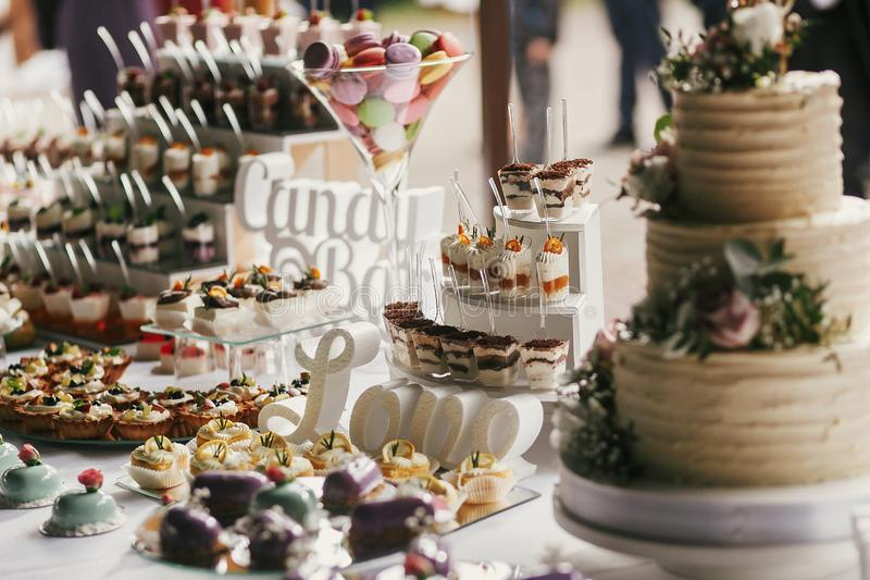 Delicious candy bar at wedding reception. White and chocolate desserts with fruits, macarons, cake, cupcakes on stand, modern stock photography