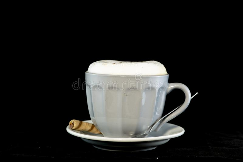 Delicious Cappuccino served with chocolate hazelnut wafer roll stock photography