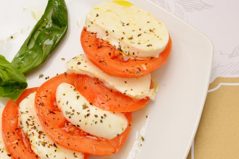 Caprese salad with ripe tomatoes and mozzarella cheese with fresh basil leaves royalty free stock photography
