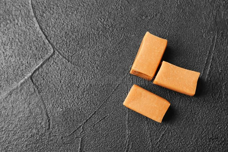 Delicious caramel candies on dark background,. Top view stock photos