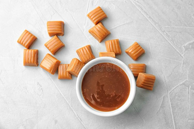 Delicious caramel candies and sauce. On light background stock photos