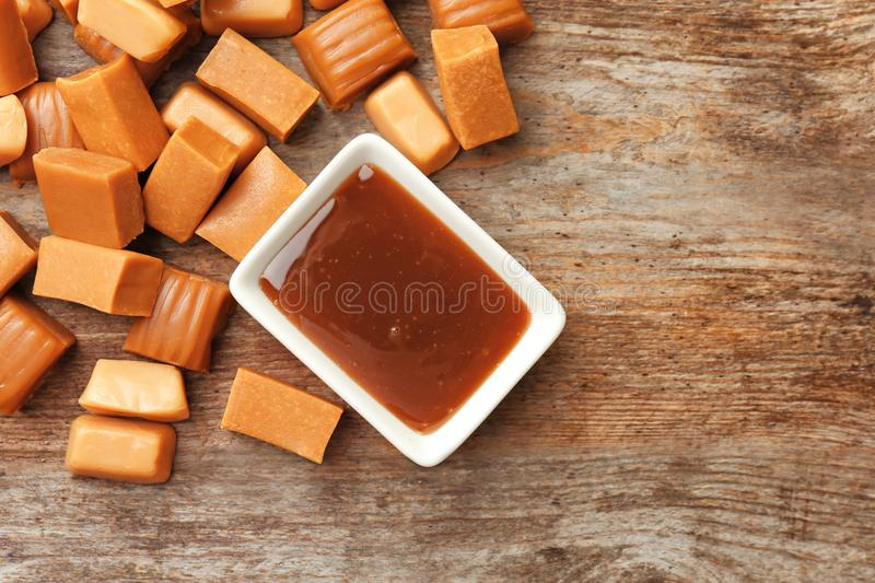 Delicious caramel candies and sauce. On wooden background royalty free stock photography