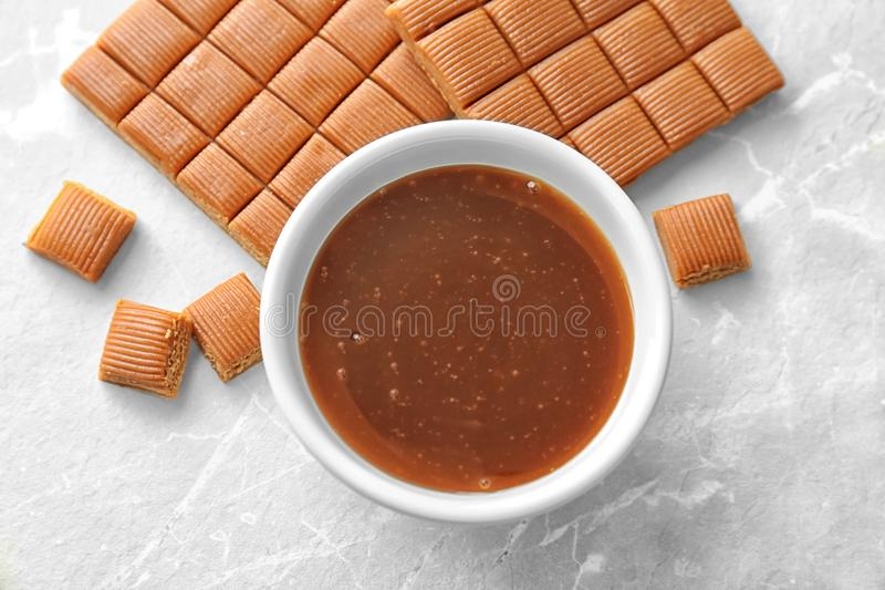 Delicious caramel candies and sauce. On light background stock image
