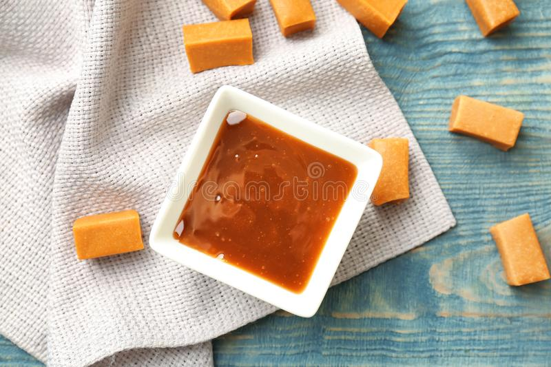 Delicious caramel candies and sauce. On wooden background royalty free stock photos