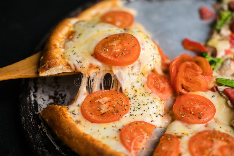 Cheese stringy slice lifted of full supreme vegan pizza baked fresh out of the oven next to ingredients royalty free stock photography