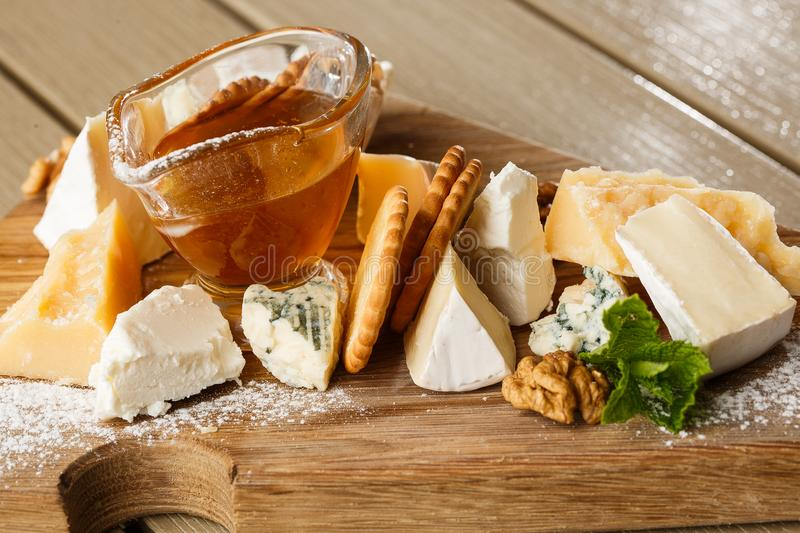 Tasting cheese dish on a wooden plate. Food for wine and romantic, cheese delicatessen on a wooden rustic table. Top stock photo