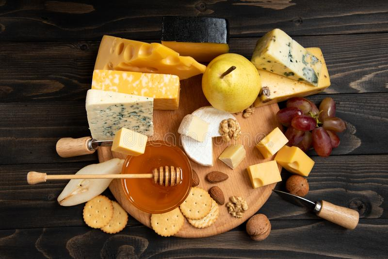 Various types of cheese on a rustic wooden table. Delicious cheese on the table. Various types of cheese on a rustic wooden table. Assortment of cheeses with royalty free stock photo