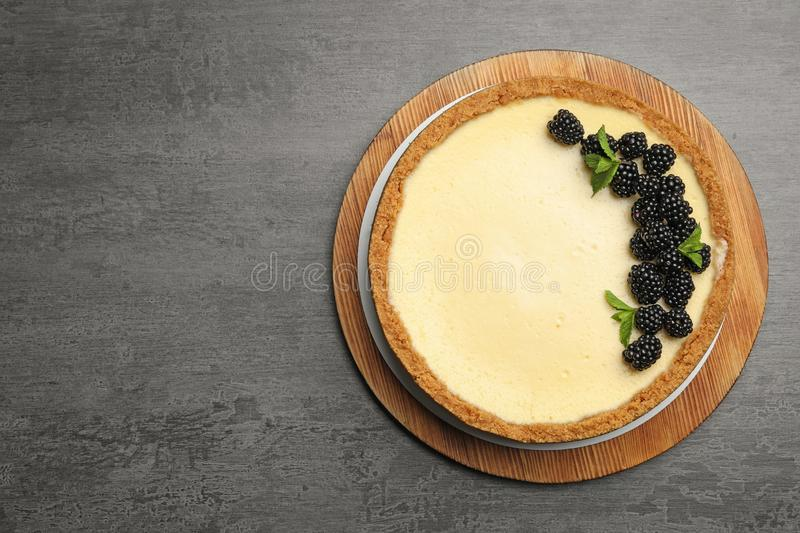 Delicious cheesecake  with blackberries on grey table, top view. Space for text. Delicious cheesecake decorated with blackberries on grey table, top view. Space stock photos