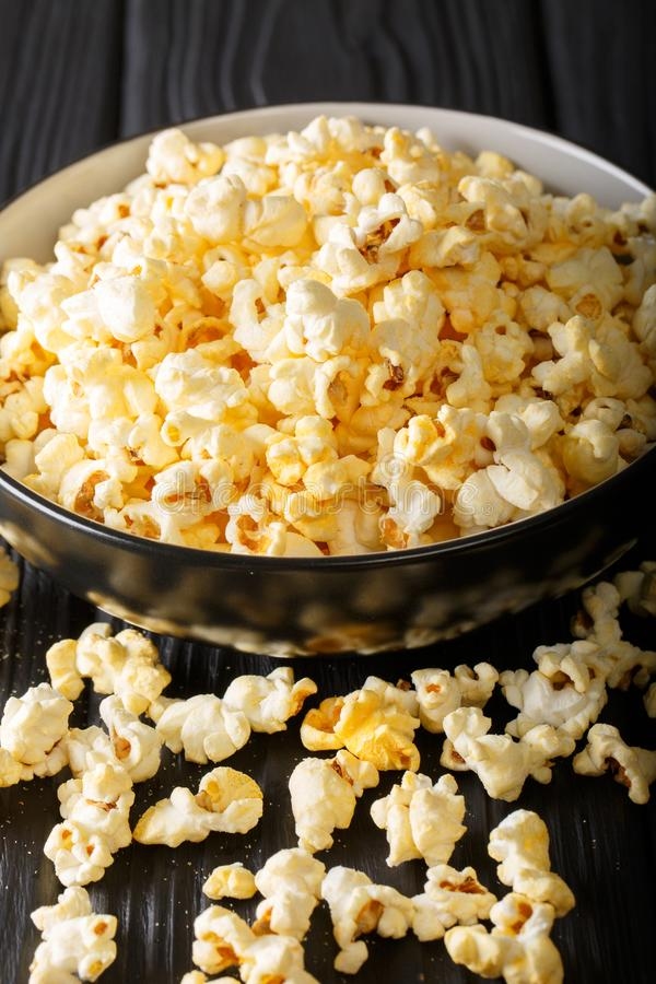 Delicious cheesy popcorn in a bowl close-up. Vertical stock photo