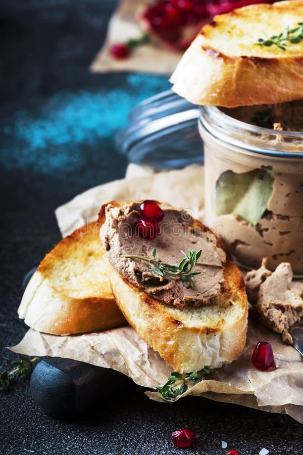 Delicious chicken liver pate on toasted bread with pomegranate seeds and thyme, dark kitchen background table, place for text, royalty free stock photography