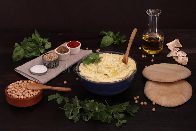 DELICIOUS CHICKPEAS HUMMUS  WITH PITA BREAD, BUCKWHEAT BREAD, OLIVE OIL AND OTHER INGREDIENTS royalty free stock photo