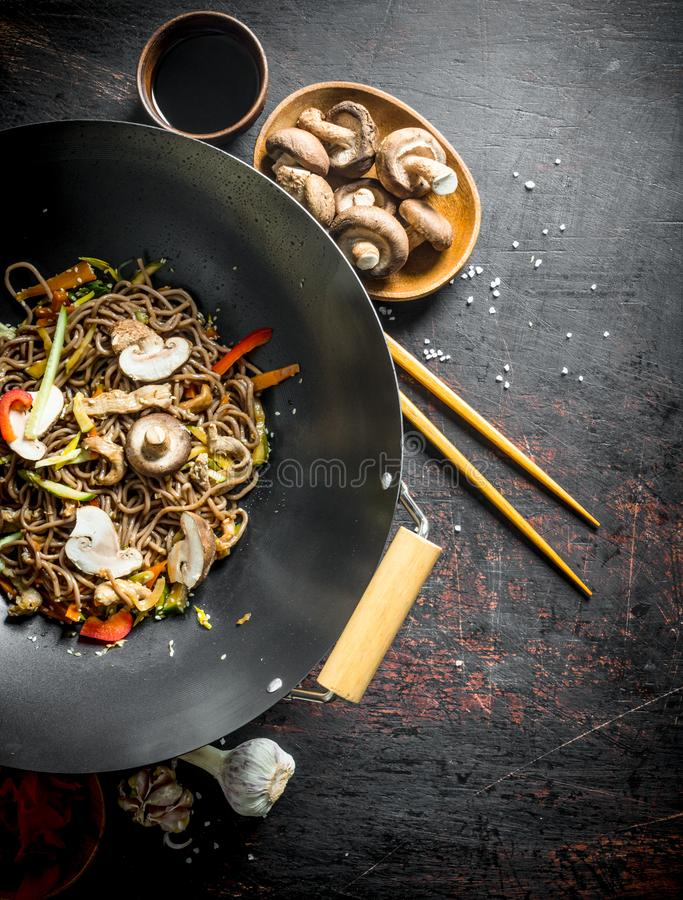 Delicious Chinese soba wok noodles with beef, mushrooms and vegetables. On dark rustic background royalty free stock photography