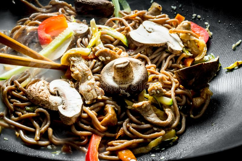 Delicious Chinese soba wok noodles with beef, mushrooms and vegetables. On dark rustic background stock photography
