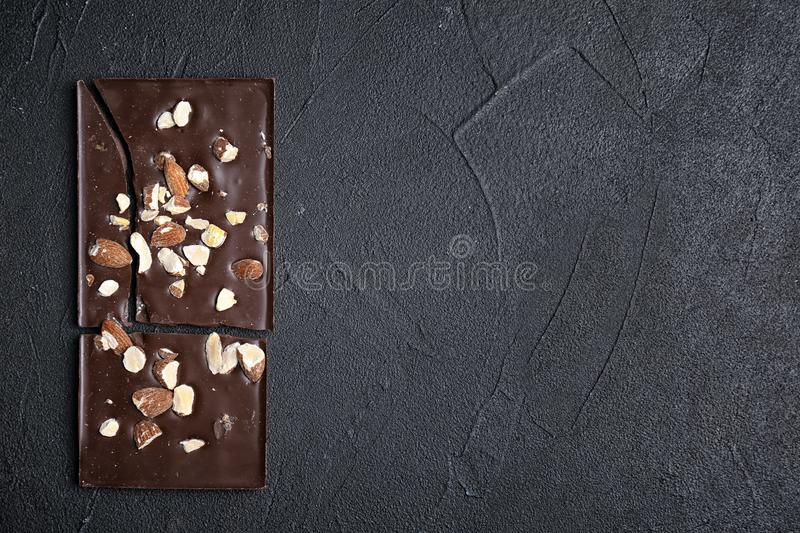 Delicious chocolate bar with nuts on dark table. Top view royalty free stock images