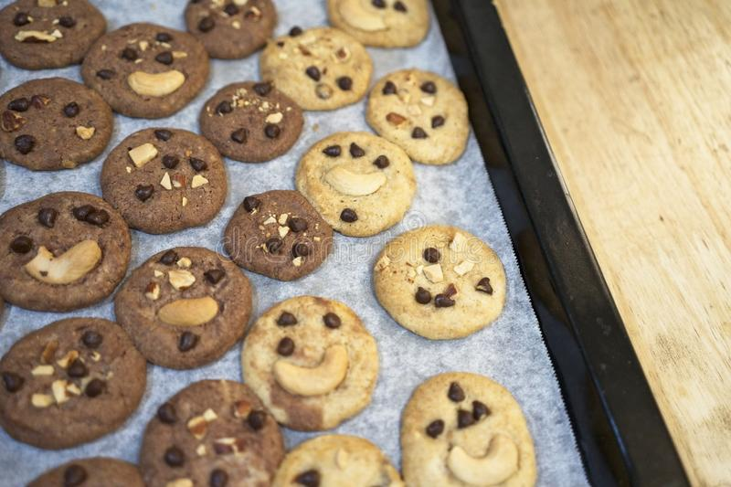 Delicious Chocolate Chip Cookies on baking tray and on wooden table, Top view stock photography