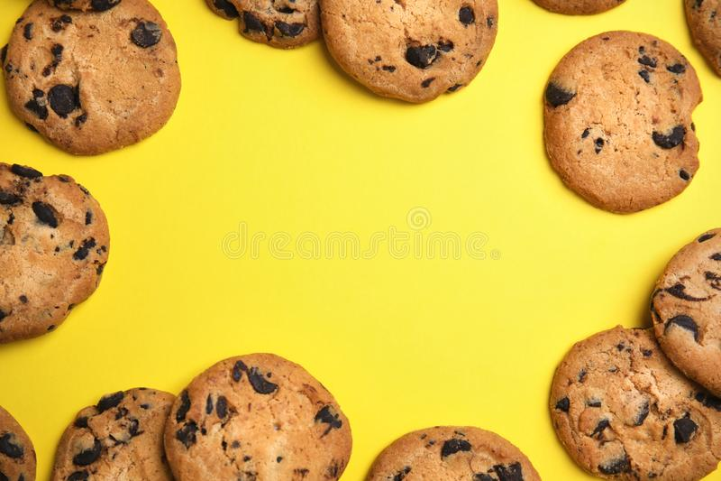 Delicious chocolate chip cookies on color background, flat lay. stock photography