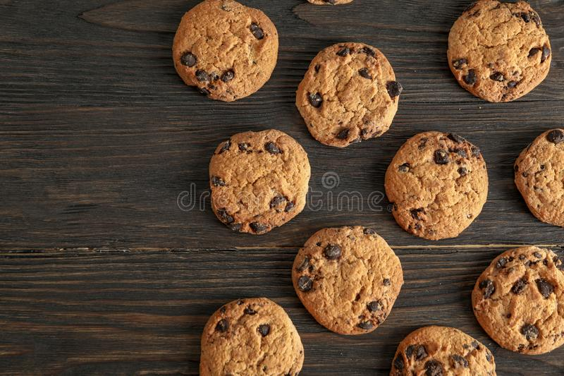 Delicious chocolate chip cookies on wooden background, flat lay royalty free stock image