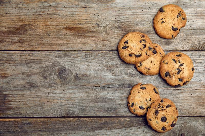 Delicious chocolate chip cookies o. N wooden table, flat lay. Space for text royalty free stock images