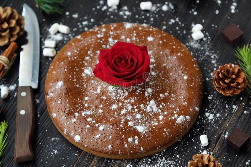 Delicious chocolate Christmas cake with a rose on the table royalty free stock photos