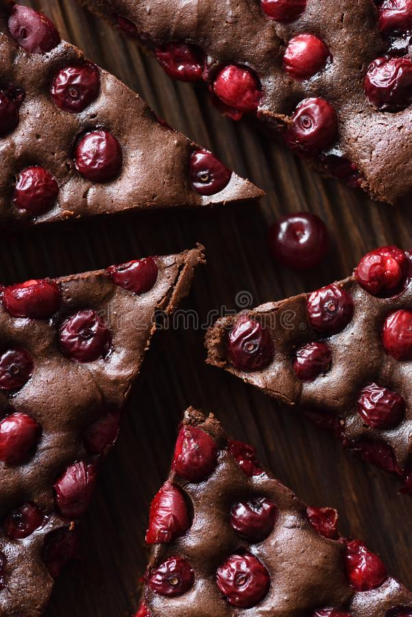 Delicious chocolate dessert. Homemade brownies with cherries on oak board shaped like labyrinth royalty free stock images
