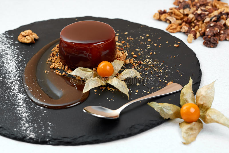 Delicious Chocolate glazed circle cake on black shale. Chocolate dessert with Walnut. Restaurant Stylized composition. Delicious Chocolate glazed circle cake on royalty free stock photo